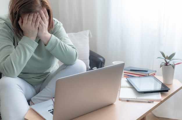 Woman hands legs freelancer table sofa laptop pc home workplace bad news upset