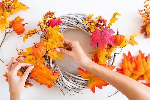 女性の手は黄色の葉からドアに秋の花輪を作る