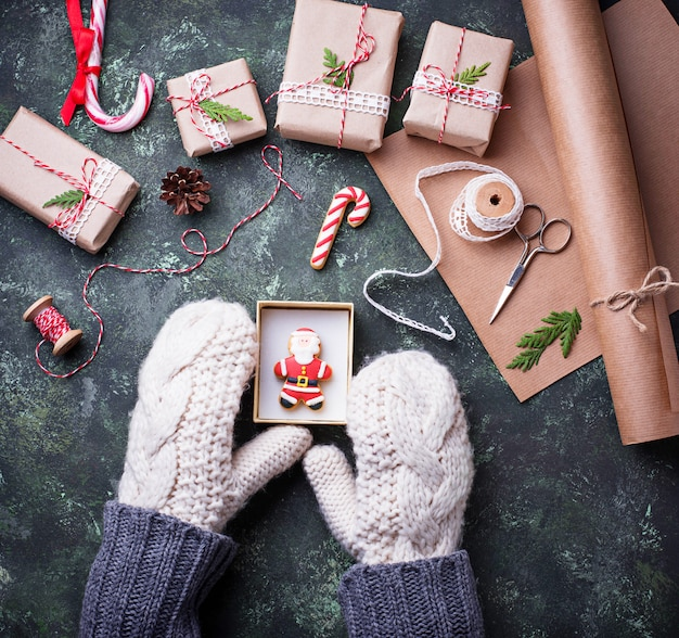 Woman hands in mittens packing boxes with christmas gifts presents. top view