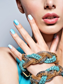 女性の手はマニキュアファッションブルージュエリーを釘付けします。
