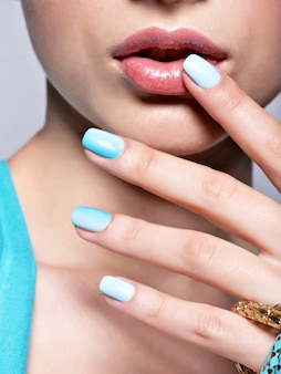 Woman hands nails manicure fashion blue jewelry.