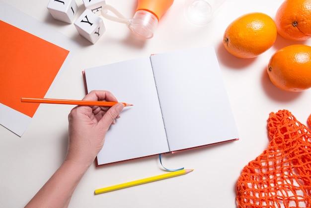 女性はノートブックとテーブルの上の新鮮なオレンジを手渡し、平らに横たわっていた