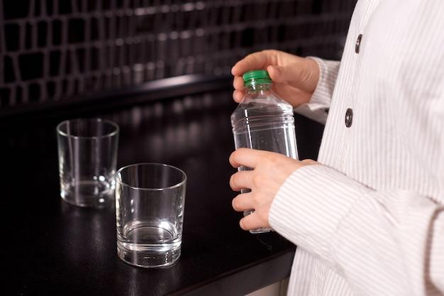 女性は朝に健康的なきれいな水を飲むためにボトルを開けます