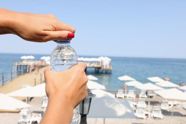 여자는 더운 계절 개념 동안 해변 음주 체제에서 야외에서 물 한 병을 엽니다.