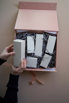 Woman hands open gift box with cosmetics