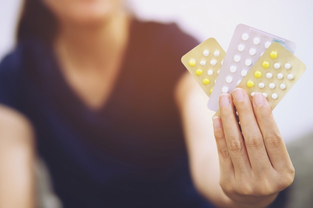 女性の手は、経口避妊薬を手に開きます。経口避妊薬を食べる。