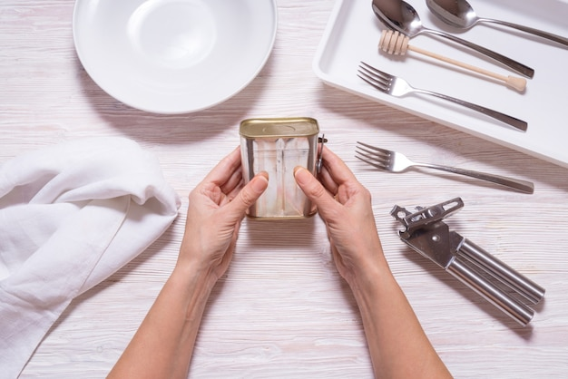 Woman hands opening tin can with corned beef, top view kitchen table
