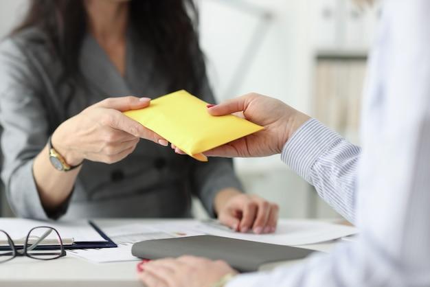 Женщина передает собеседнику полный конверт. заработная плата в концепции конверта