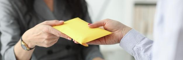Женщина передает полный конверт своей зарплате собеседника в концепции конверта