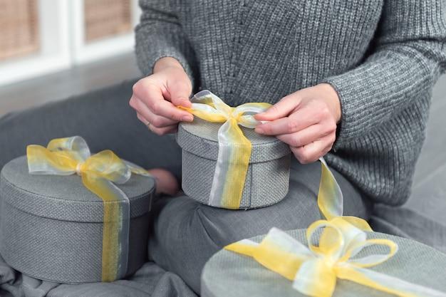 여자 손 팩 선물, 회색 둥근 상자 노란 리본