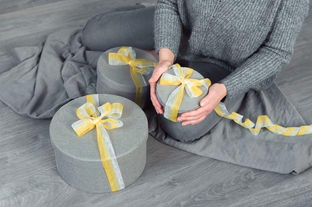 Женщина руки пакет подарков, серая круглая коробка желтая лента