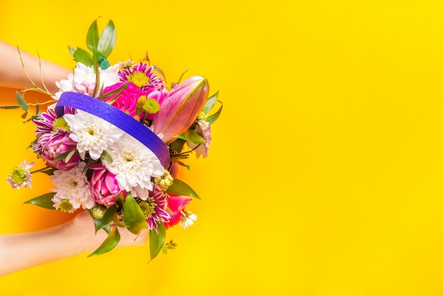 Woman hands pass bouquet, yellow background, copy space