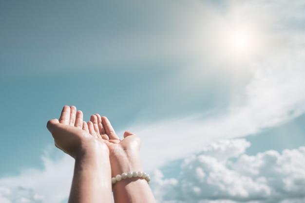 自然の青い空の背景の前で祈るように女性の手が一緒に配置されます。