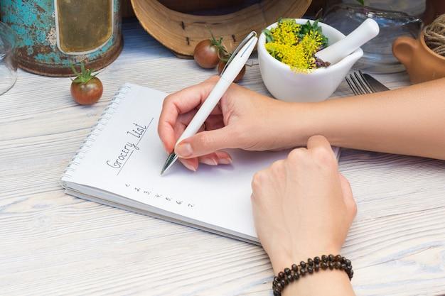 食料品のリストを計画する女性の手
