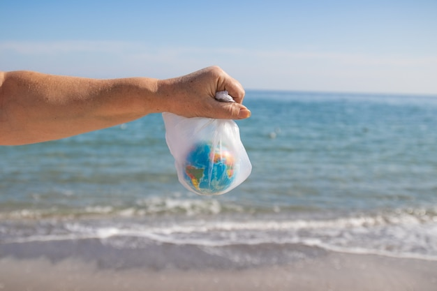 Woman hands a plastic bag and planet earth on sea background.