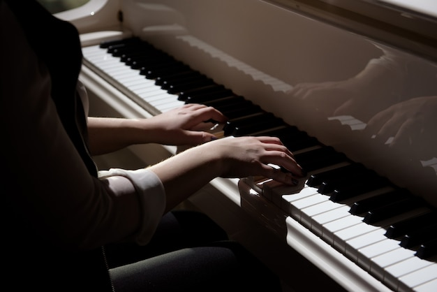 Woman hands playing a piano, musical instrument.