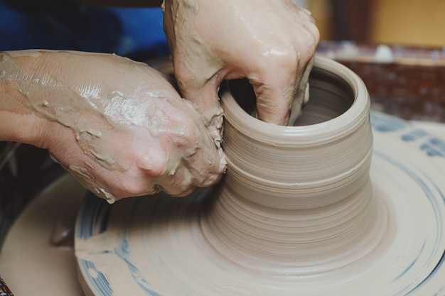 Woman hands on pottery wheel. craftsman artist shapes pot