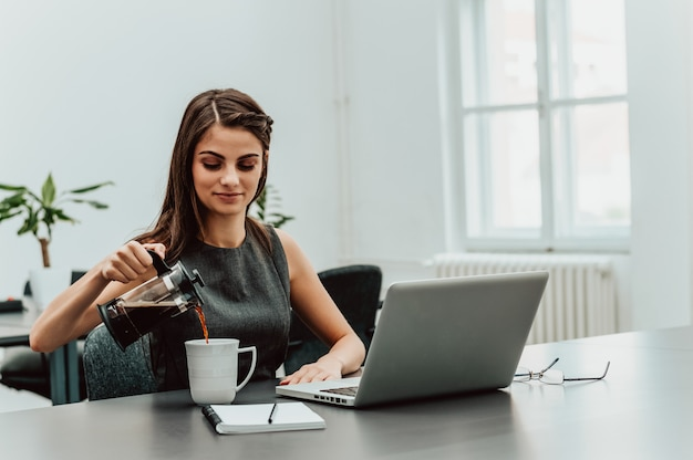 Woman hands pouring coffee into glass cup on office table.