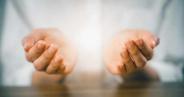Woman hands praying (makes a dua) and light on palm.