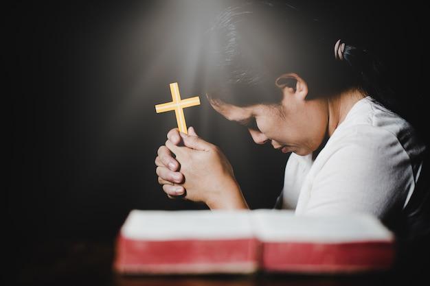 나무 테이블 위에 어둠 속에서 십자가와 성경으로기도하는 여자 손
