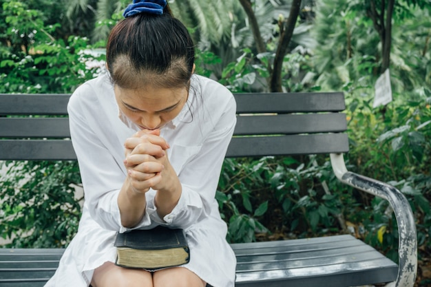 Woman hands praying with a bible in her knees outdoors