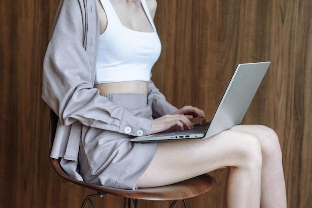 여자 손은 인터넷과 기술을 사용하여 노트북에 인쇄합니다.