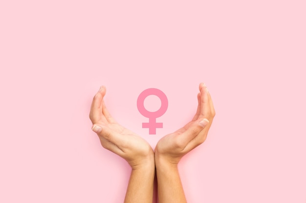 Woman hands protecting female sign on a pink background