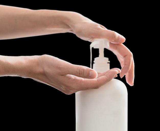 コピースペースと黒い壁に分離されたポンプのプラスチック石鹸のボトルを押す女性手