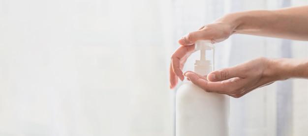 コピースペースと白い背景の上のポンププラスチック石鹸ボトルを押す女性手