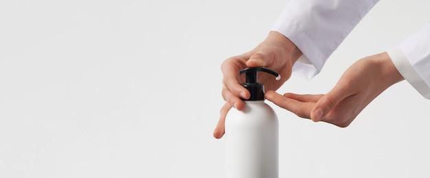 女性の手は、手洗い消毒剤ゲルポンプディスペンサーを使用して、コピースペース付きのポンププラスチック石鹸ボトルを押します。細菌、細菌、ウイルスを殺す