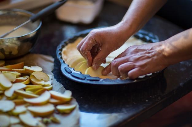 Woman hands put apples on dough