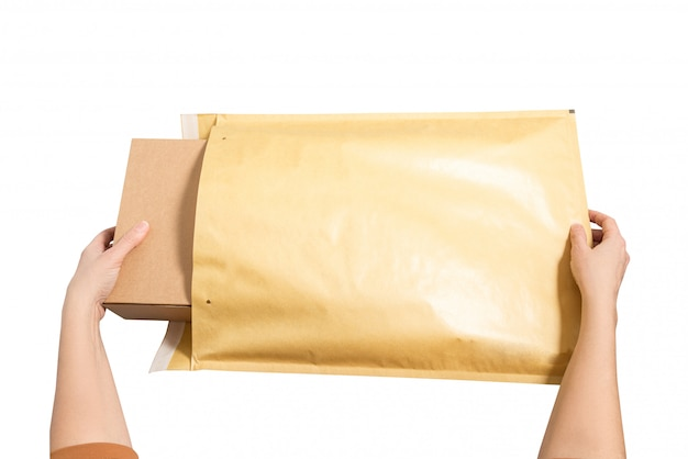 大きな郵便封筒の中に段ボール箱を置く女性の手