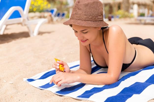 여자 손 suncream 병에서 자외선 차단제를 넣어.