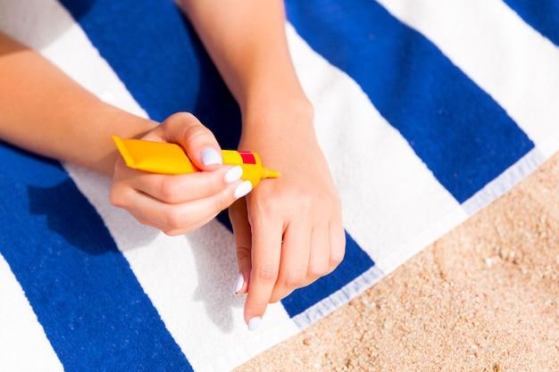 Woman hands putting sunscreen from a suncream bottle.