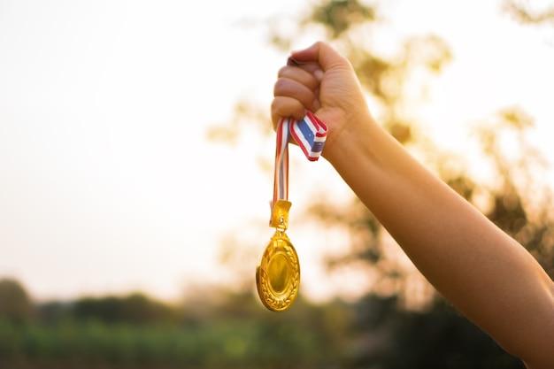 여자 손을 제기 하 고 태국 리본으로 금메달을 들고