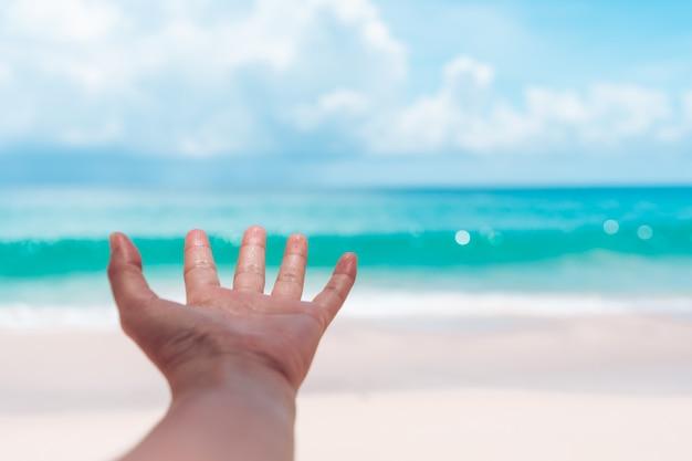 女性の手はビーチや青い海に手を伸ばします。