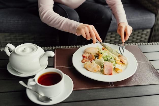 Женщина готовится съесть салат цезаря и пить чай в ресторане