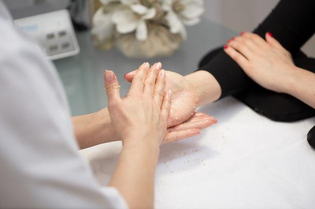 ビューティーサロンで美容師によるハンドスクラブピーリングを受けた女性の手。 spaマニキュア、ハンドマッサージ、ボディケア