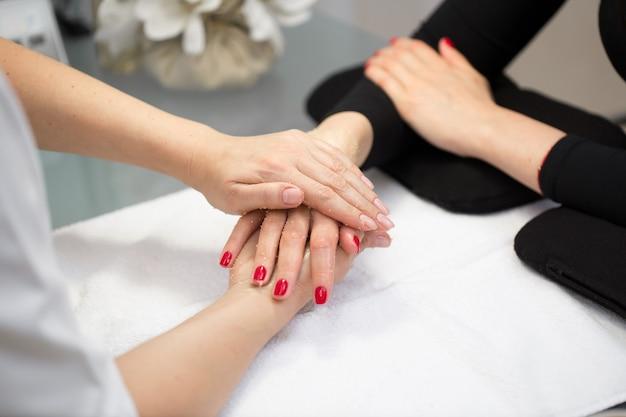 Женщина руки получает пилинг скраб для рук косметолог в салоне красоты. спа-маникюр, массаж рук и уход за телом