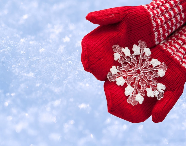 Woman hands in red gloves holding white big snowflake