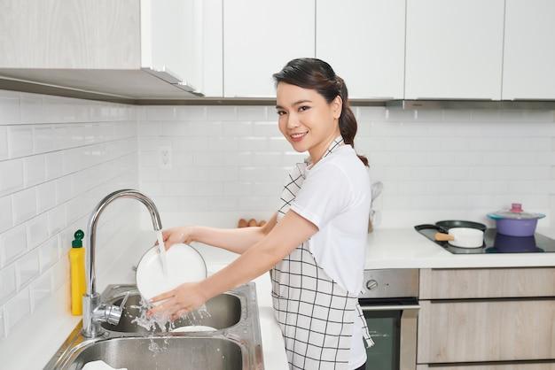싱크대에서 흐르는 물에 여자 손 헹굼 접시