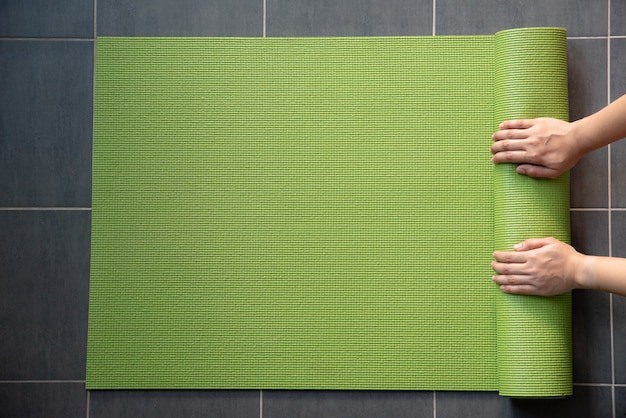 Woman hands rolling green yoga mate on the floor.