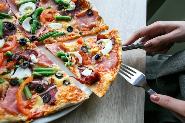 女性の手豆、チーズ、ハム、卵、ペパロニ、野菜で新鮮なピザをスライスします。ピザを切る