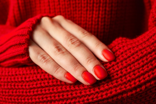 Woman hands, stylish red manicure, space for text. closeup