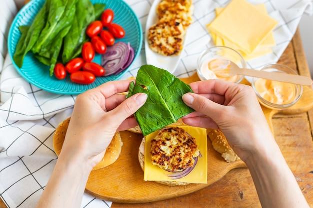 Руки женщины берут булочку с начинкой и выкладывают салат поверх котлеты.