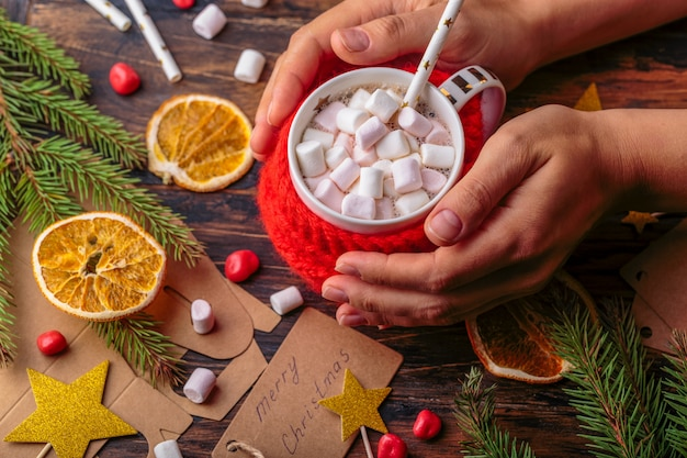 Woman hands takes a mug of hot cacao with marshmallows knitted cloth for a mug christmas concept winter background of packing gifts christmas decoration