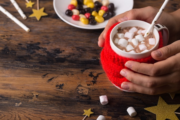 Woman hands takes a mug of hot cacao with marshmallows knitted cloth for a mug christmas concept winter