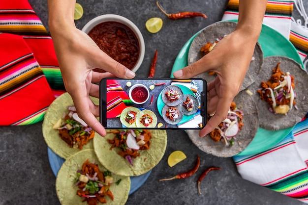 Руки женщины фотографируя мексиканские тако