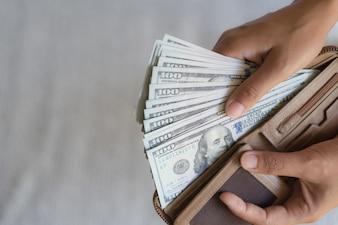 女は手を出して手を出すアメリカドル紙幣を財布から