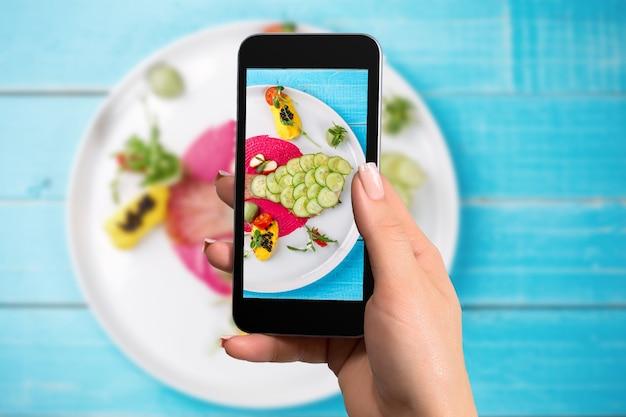 스마트폰으로 혼합 야채와 함께 사진 물고기를 찍는 여자 손